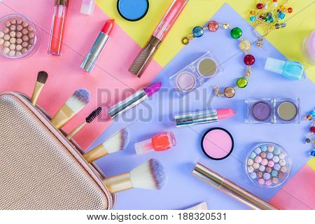 Colorful make up products with golden pursue close up material design flat lay scene