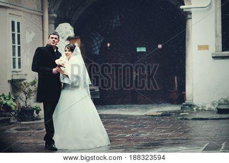 Beautiful Wedding Couple Stands On The Backyard Enjoying The Snow