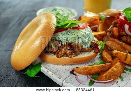 Delicious Bagel Pork sandwiches with vegetable and Tzatziki Sauce and Fries on white board