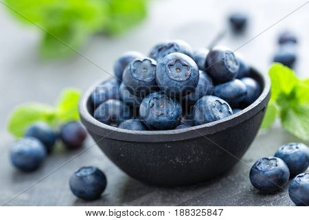 Fresh Blueberries in a bowl on dark background top view. Juicy wild forest berries bilberries. Healthy eating or nutrition.