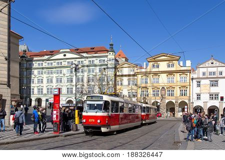 Prague, Czech Republic - March 16, 2017: An old red tram at a station with people waiting