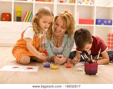Woman having fun with kids laying on the floor painting hands-focus on the girl face