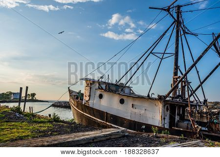 An old fishing boat docked along the shoreline in Middletown NJ.