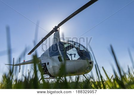 Small Robinson R22 light utility helicopter parked on grass airport. One of the world's most popular light helicopters with twin blades and a single engine