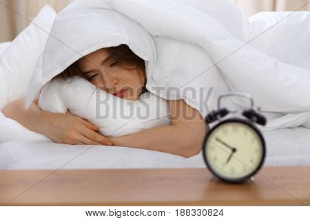 Beautiful young woman sleeping lying in bed and relaxing in the morning. A sunny day starts is the time to go for a work or sleep on the weekends