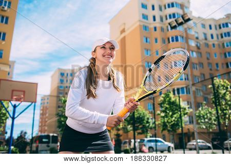 woman playing tennis, holding tennis racket. Practicing tennis on the tennis court at sunny day
