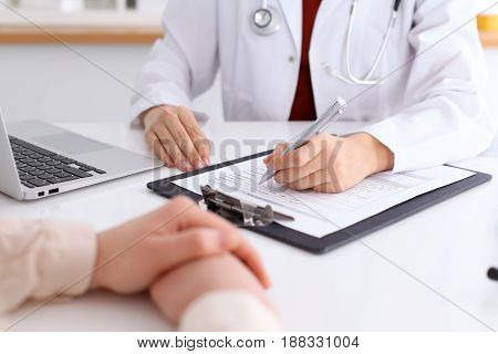Close up of a female doctor filling up  an application form while consulting patient. Medicine and health care concept