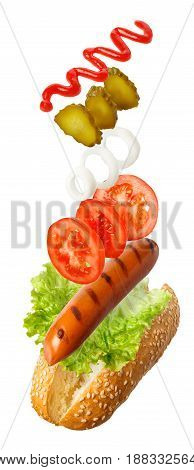 ingredients for hot-dog falling in the air isolated on white - grilled sausage, fresh vegetables, ketchup. Fly fast food