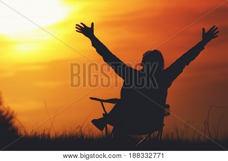 Silhouette of relaxed woman enjoying sunset time, sitting in the chair outdoors, raising hands to the sky. Travelling and vacation concept.