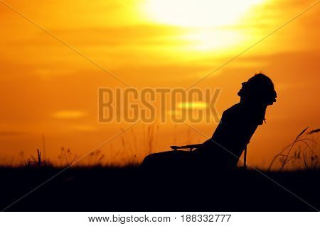 Silhouette of happy relaxed woman enjoying sunset time, sitting in the chair outdoors. Travelling and vacation concept.