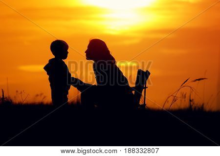 Silhouettes of young mother sitting on chair and son standing next to, looking to each other. Mom and son having fun outdoors on sunset time. Happy family relations concept.