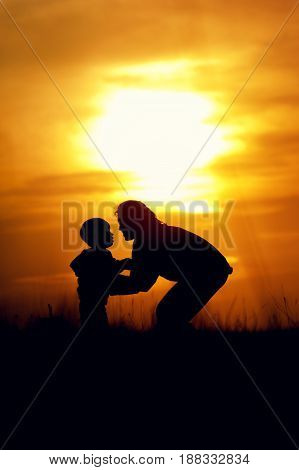 Silhouettes of young mother sand son standing next to. Mom and son having fun outdoors on sunset time. Happy family relations concept.