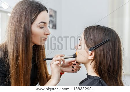 professional makeup artist doing makeup for young girl. Girl works in beauty salon. Visagiste applying liquid tonal foundation cream on the face skin with brush. Backstage photo