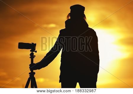 Silhouette of professional female photographer standing with modern camera and tripod against setting sun. Travelling and tourism concept.