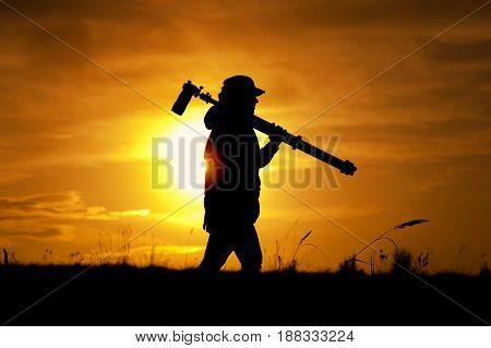 Silhouette of female photographer holding photo camera and tripod and walking outdoors. Setting sun background. Travelling and tourism concept.