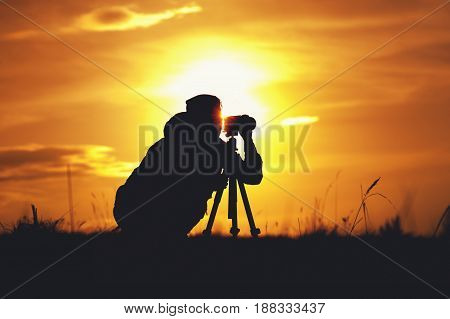 Silhouette of professional female photographer working with camera and tripod, taking landscape shots during sunset. travelling and tourism concept.