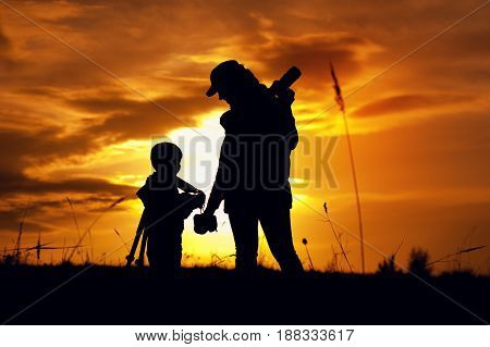 Happy family relationship. Silhouetttes of mother photographer and little son with camera and tripod getting ready to taking pictures at sunset time.