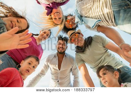 cute kids and parents with friends in a circle looking down. group of family friends and children looking from above. ultra wide angle.