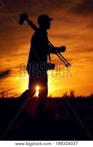 Silhouette of young male photographer holding camera and tripod, standing against setting sun. Travelling and tourism concept.