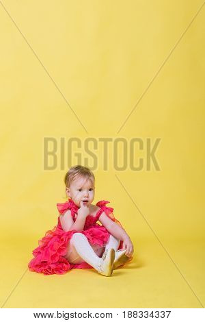 Girl toddler in a pink dress on a yellow background wearing the shoes on his feet.