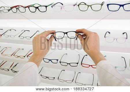 Ophthalmologist holding glasses for correction of vision, in the background white showcase with glasses