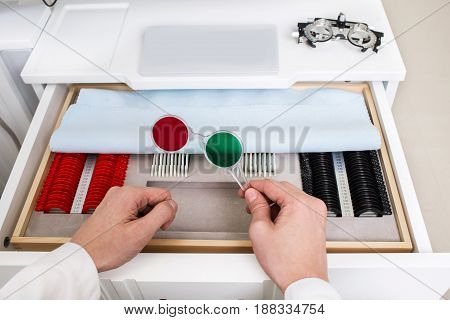 Optometrist prepares a set of ophthalmic trial lenses for vision testing, open table with optometric instruments, top view