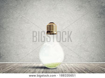 Glass light bulb in concrete empty room. Eco concept
