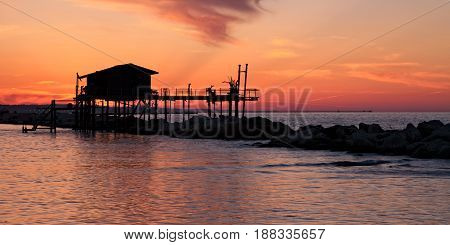 Stilt house over the sea in a beautiful red sunset