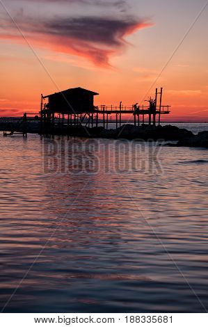 Stilt house in silhouette over the sea in a beautiful red sunset