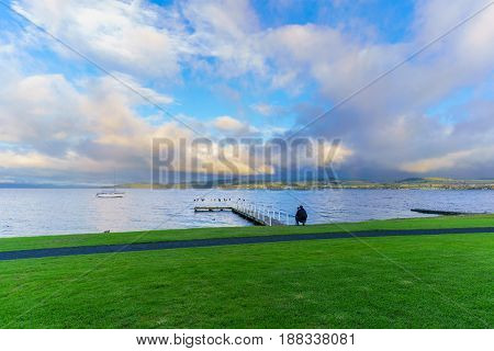 Young male photographer taking picture of Lake Taupo in the morning North Island of New Zealand