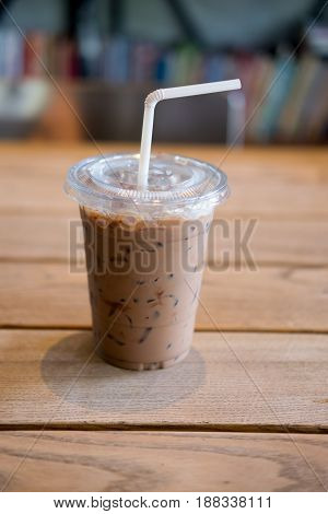 Iced mocha with straw in plastic cup on wooden table