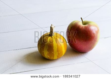 Decorative pumpkin and apple on white wooden background
