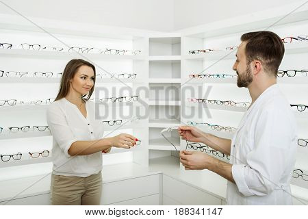 woman chooses eyeglasses to correct vision standing at ophthalmological store near shelf with many glasses. Ophthalmologist consults and helps the visitor to choose glasses for vision correction