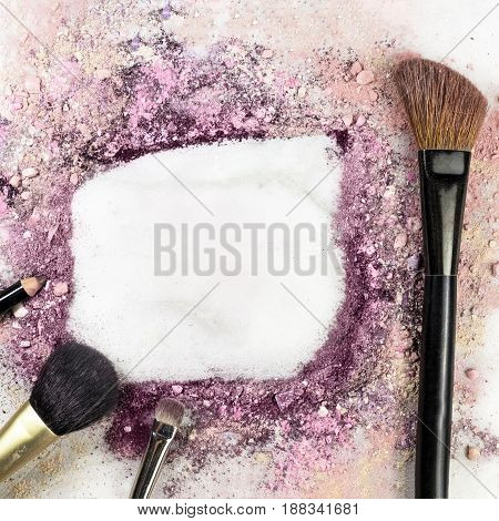Makeup brushes and pencil on white marble background, with traces of powder and blush forming a frame. A square template for a makeup artist's business card or flyer design, with copy space
