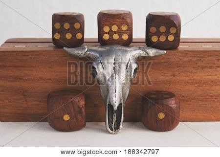 Composition of a trinket of a bull's skull and dice.