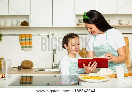 Mother teaches her daughter how to cook food, standing at white kitchen, Smiling and looking in the book of recipes. Family leisure at home