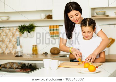 Mother teaches her daughter how to prepare breakfast from fruit, standing at white kitchen, Smiling and cutting orange. Family leisure at home