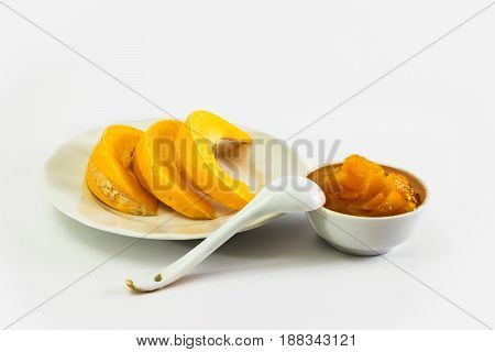 Sliced pumpkin on a plate and Pumpkin jam in saucer. Folk recipes. Sweet dessert. Isolated on white background.