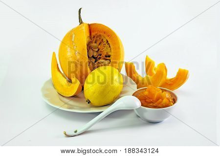 jelly-glass with a Pumpkin jam pumpkin and slices of pumpkin. Sweet dessert. Isolated on white background.