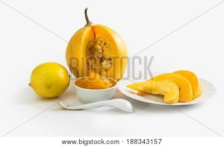 jelly-glass with a Pumpkin jam pumpkin and slices of pumpkin. Folk recipes. Sweet dessert. Isolated on white background.