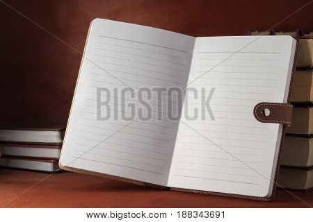 A Notebook With Textbooks On A Wooden Table.