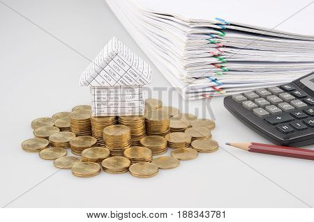 House On Pile Of Gold Coins With Pencil And Calculator