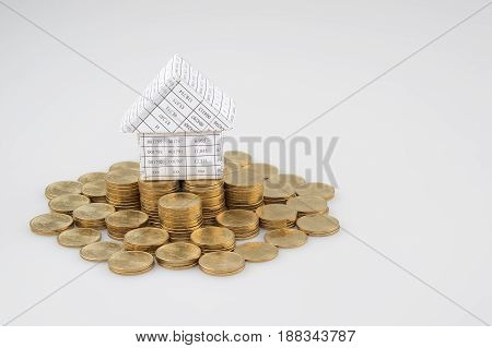 Paperwork As House Place On Pile Of Gold Coins