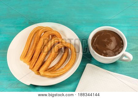 A plate of churros, traditional Spanish, especially Madrid, dessert, particularly for Sunday breakfast, with a cup of hot chocolate, on a vibrant blue table with a place for text