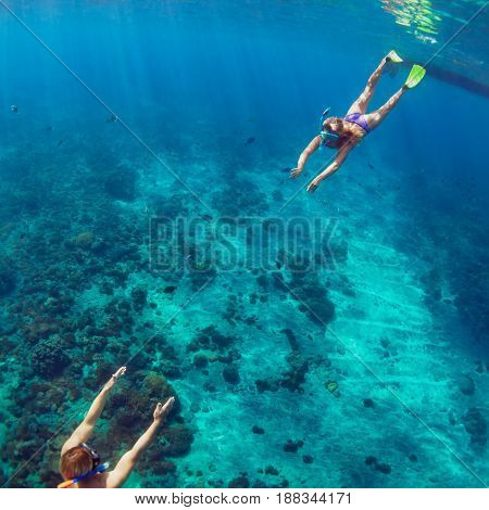 Happy family - couple in snorkeling masks dive deep underwater with tropical fishes in coral reef sea pool. Travel lifestyle outdoor water sport adventure swimming lessons on summer beach holiday