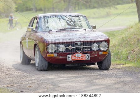 STOCKHOLM SWEDEN - MAY 22 2017: Purple Alfa Romeo 1750 classic car from 1967 driving on a country road in the public race Gardesloppet in the forests at Djurgarden Stockholm Sweden. May 22 2017
