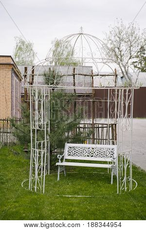 Cute wrought-iron gazebo with wrought-iron white bench standing in garden
