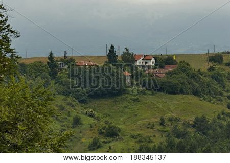 Scene with mountain glade, forest and residential district of bulgarian village Plana, mountain, Bulgaria