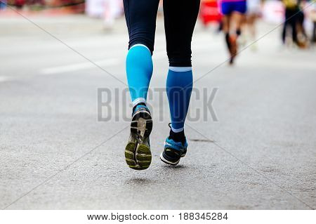 back feet woman runner in blue compression socks running street
