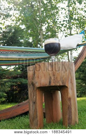 Hammock and a Beer. A colorful garden hammock rests in the shade with a cold beverage nearby